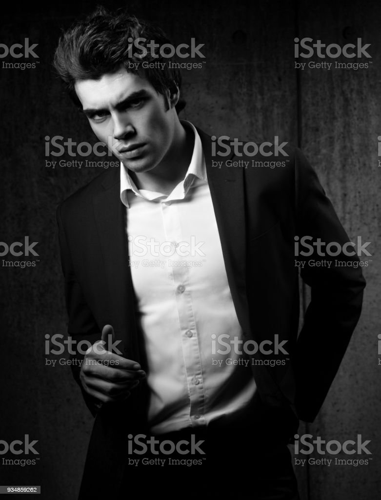 c4431be2 Sexy handsome male model posing in black fashion suit and white style shirt  on dark shadow