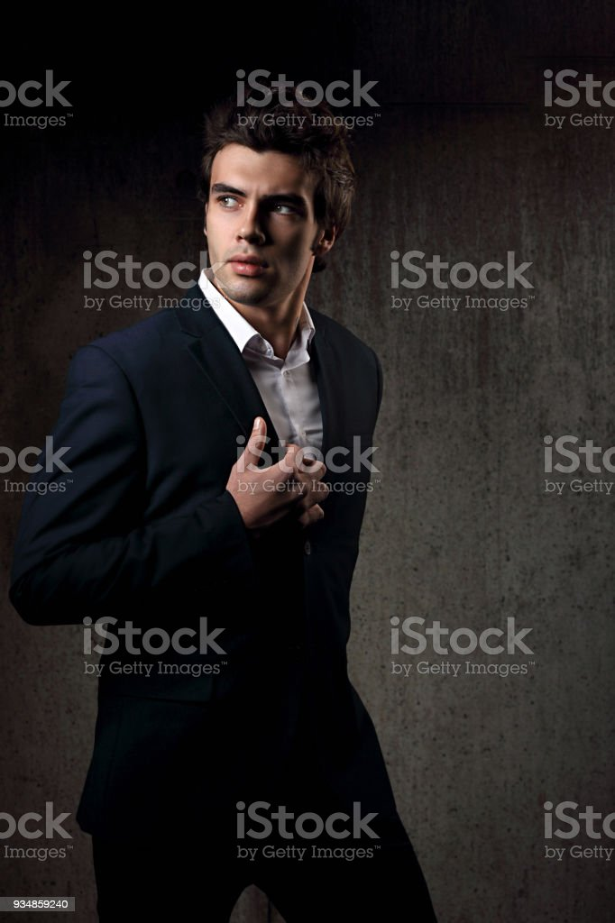 91c1273f Sexy handsome male model posing in blue fashion suit and white style shirt  on dark shadow