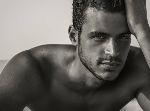 Sexy handsome male model with beautiful eyes staring into the camera. Man beauty portrait. Closeup of a hot young man in his 20s looking at the camera with a deep gaze. He is shirtless laying on the beach. shirtless male models stock pictures, royalty-free photos & images