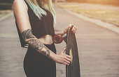 Beautiful, sexy hipster girl in tattoos against a background street wall with a long board.