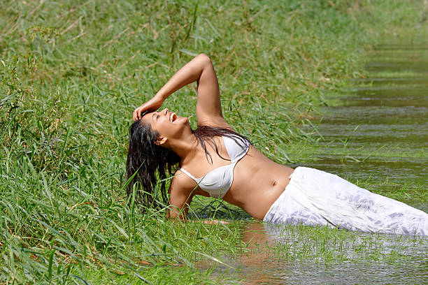 sexy indian woman laughing in the water stock photo