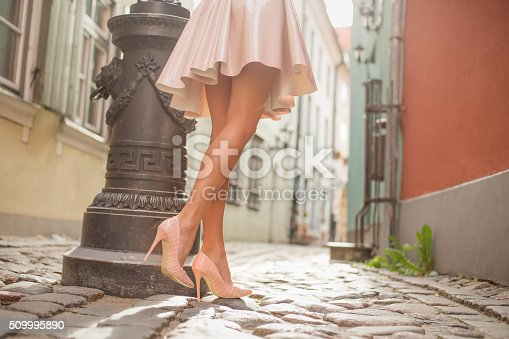 istock Sexy lady with beautiful legs walking in old town 509995890