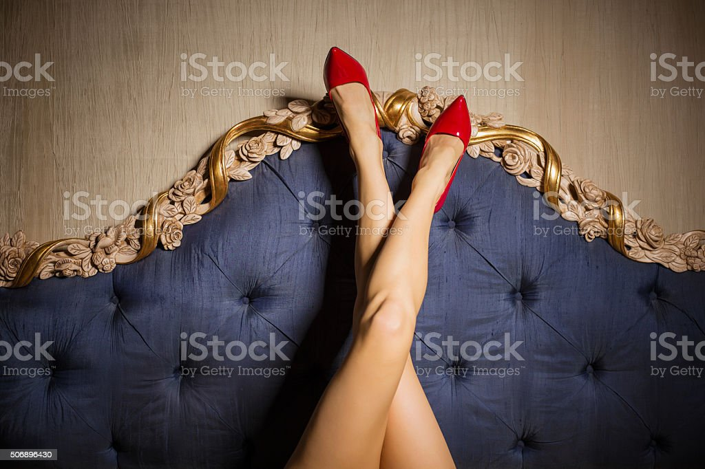 Sexy legs against beds backboard stock photo
