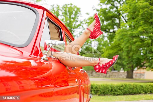 istock Sexy legs hanging out of red retro car 611089720