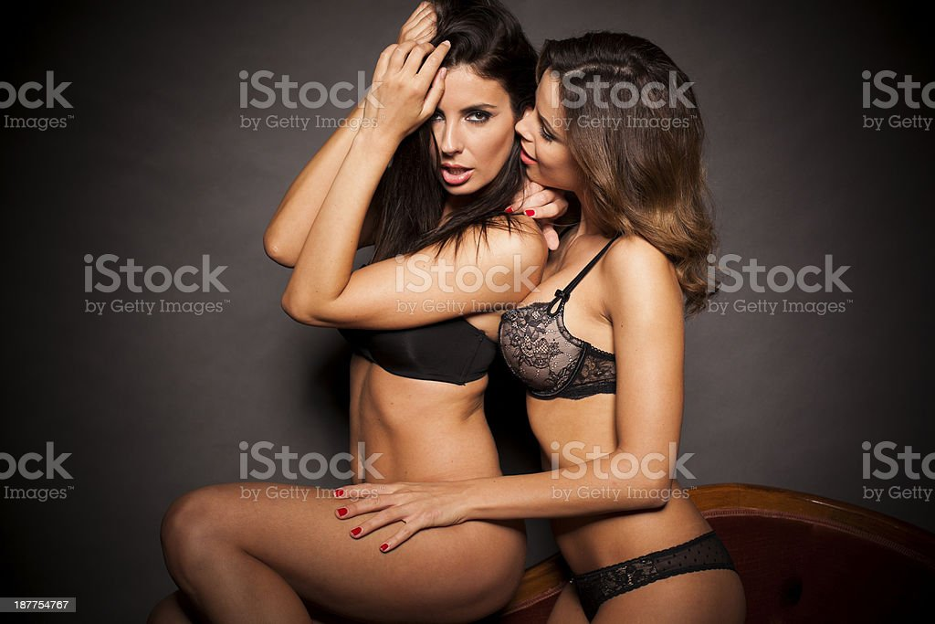 Sexy lesbian couple in lingerie on gray background royalty-free stock photo