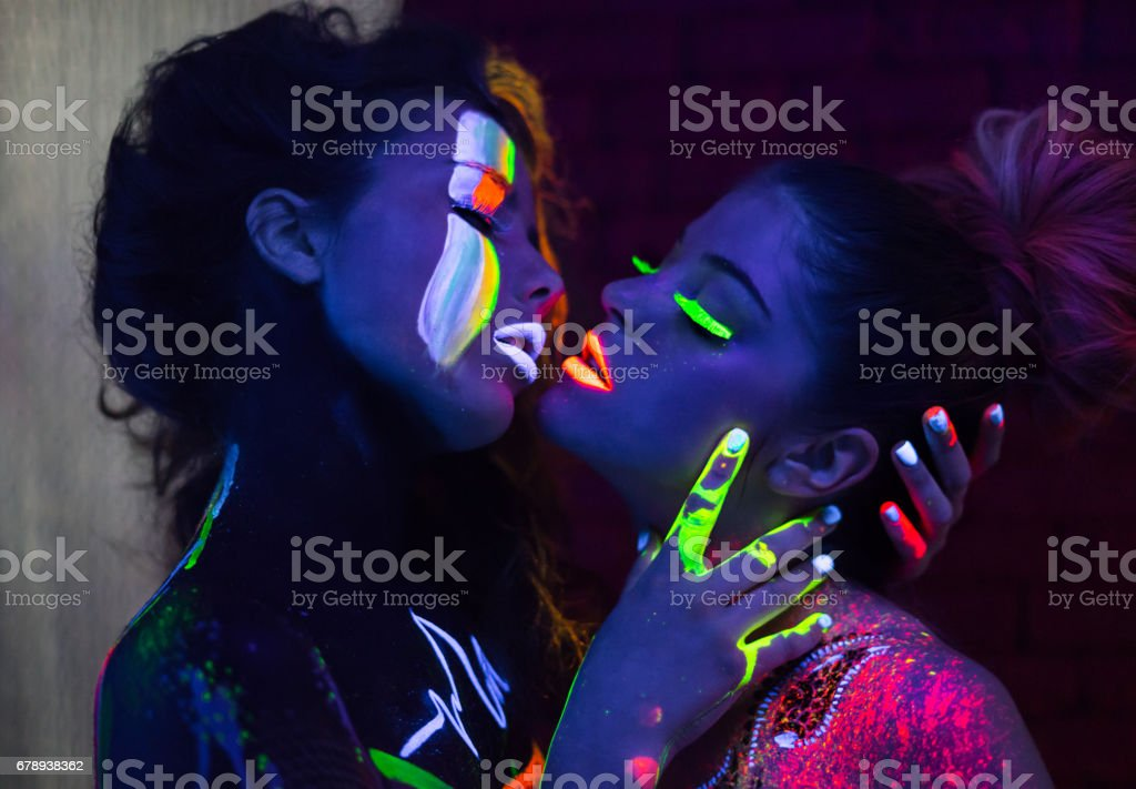 Sexy lesbian fashion models kissing in uv neon light royalty-free stock photo