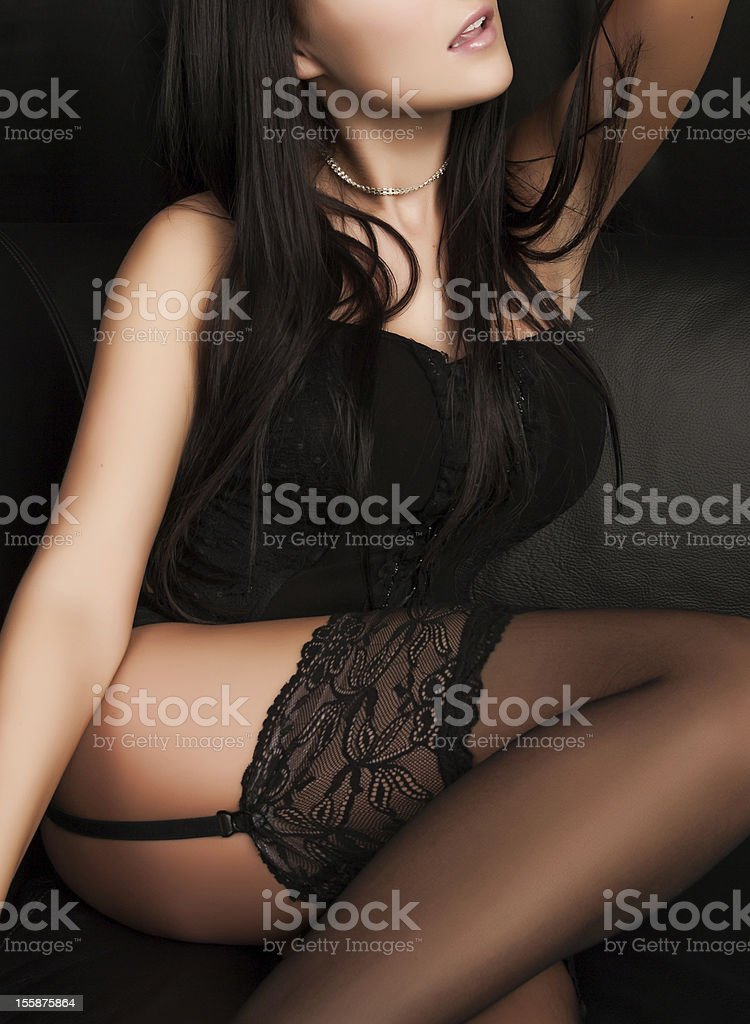 Sexy Lingerie - Woman sitting on Black Couch stock photo