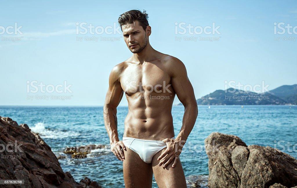 8181597904 Sexy modelo masculino en ropa interior en un escenario al mar foto de stock  libre de