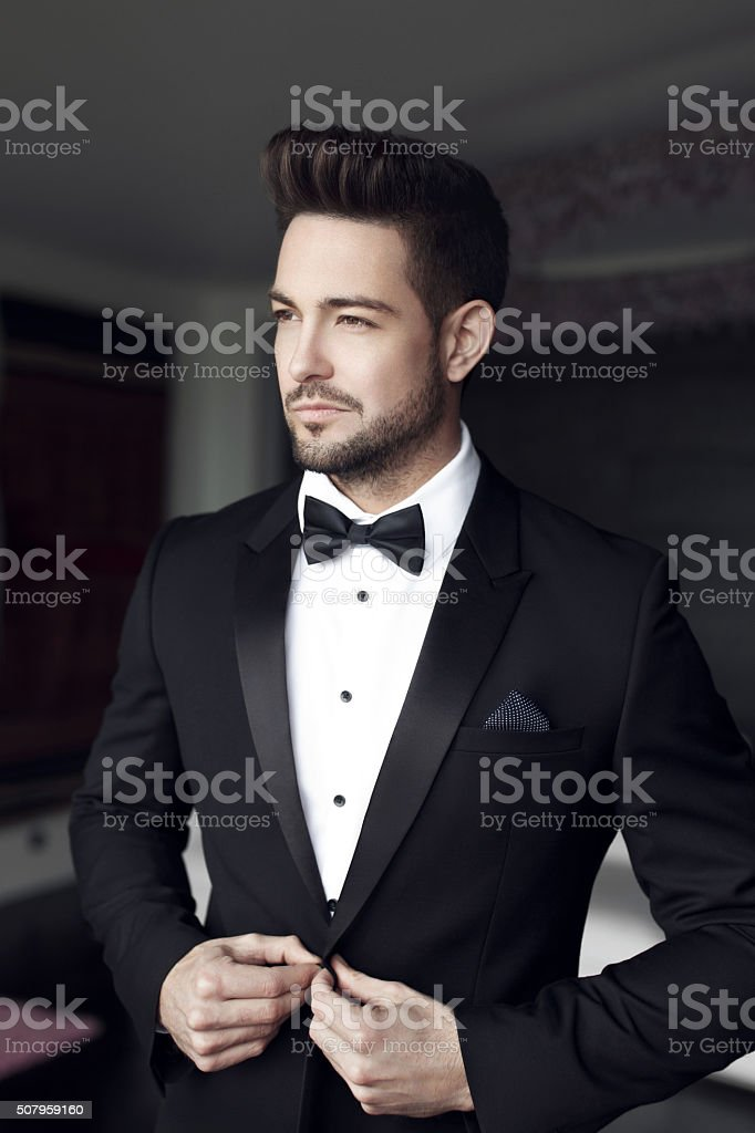 Sexy man celebrity in tuxedo indoor stock photo