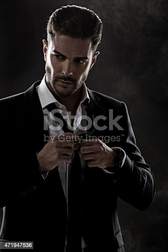 istock sexy man fixing his tie 471947536
