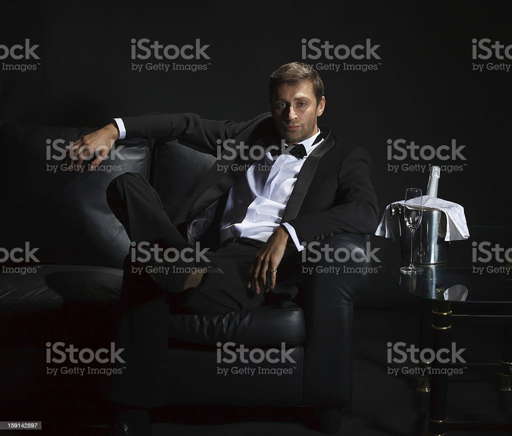 Sexy man in tuxedo waiting with champagne on a couch stock photo