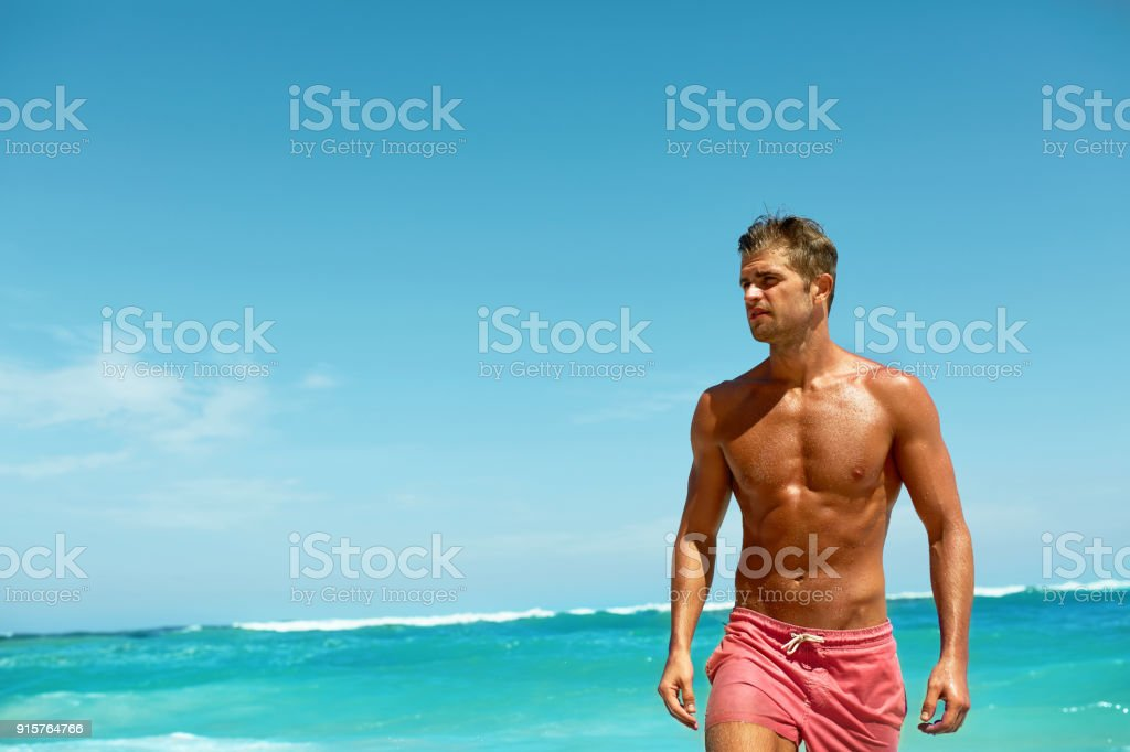 Sexy Man On Beach In Summer. Male Relaxing Near Sea stock photo