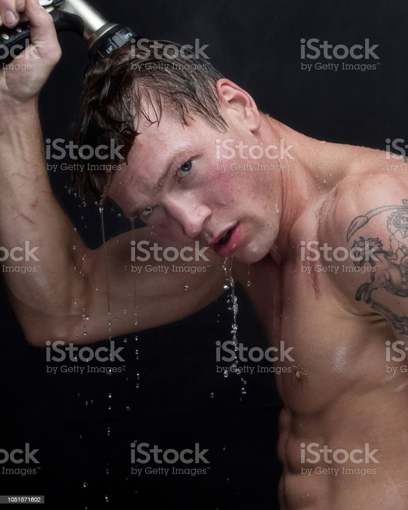 Sexy man taking a shower with a hose stock photo