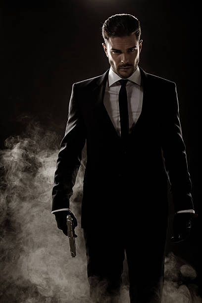 sexy man walking holding gun - killer stock photos and pictures