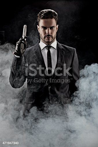 471947536 istock photo sexy man wearing suit holding gun 471947340