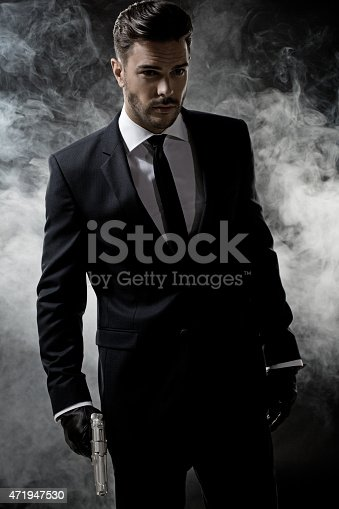471947536 istock photo sexy man wearing suit holding gun 471947530