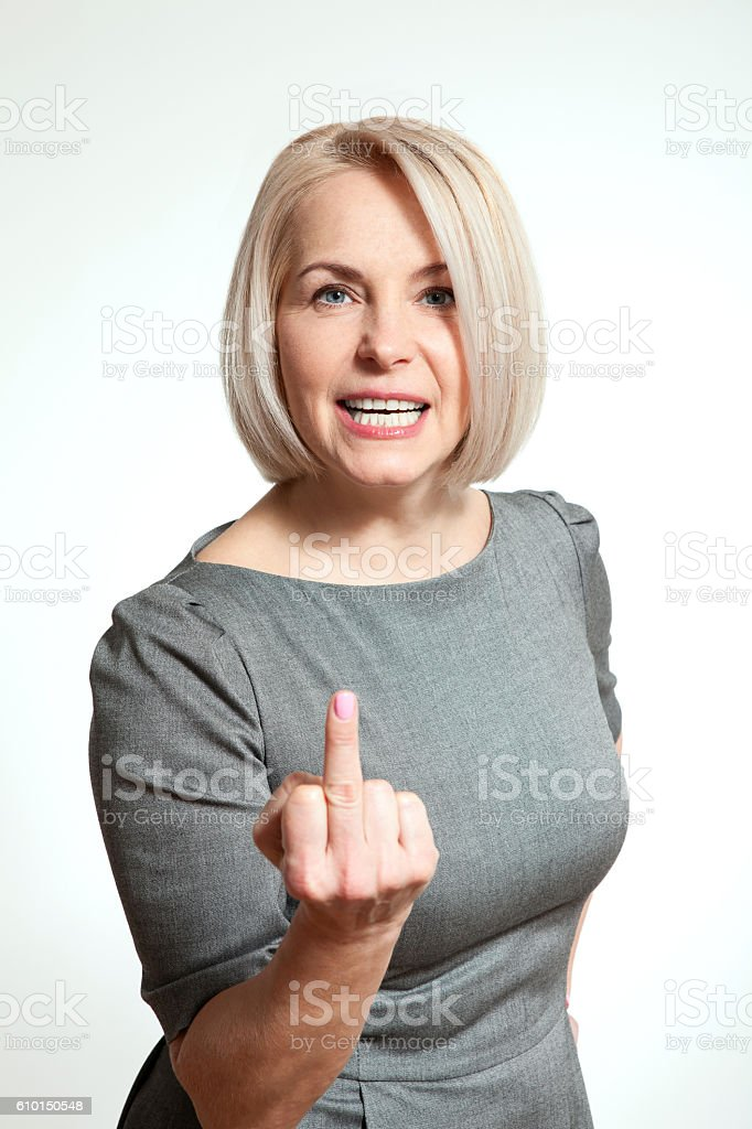 Sexy middle aged woman shows sign of fuck off. stock photo