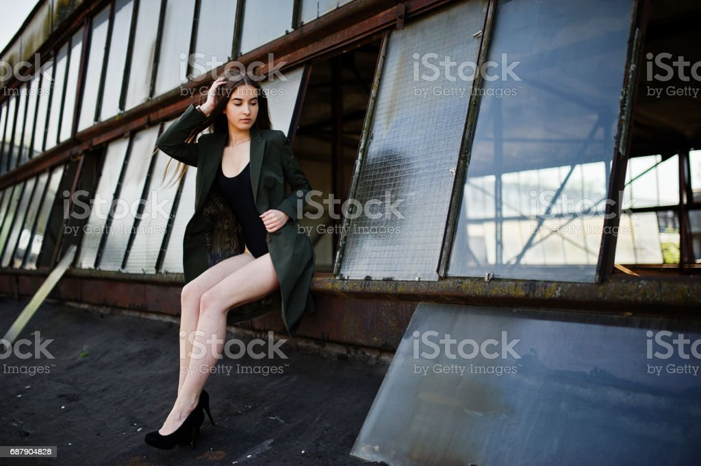 eef358f9c2 Sexy model girl wit long legs at black lingerie outfit body swimsuit  combidress and jacket posed at the roof of abadoned industrial place with  windows.
