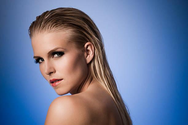 sexy model mit nassen haaren vor einem blauen hintergrund. - frisuren für schulterlanges haar stock-fotos und bilder