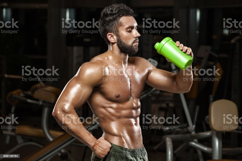 Sexy muscular man drinking water in gym, naked torso abs stock photo