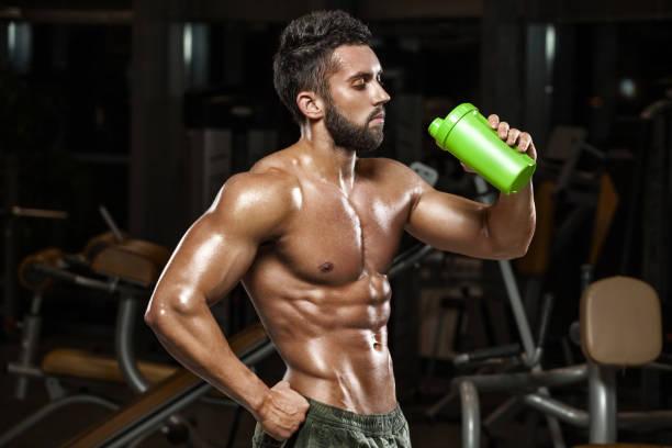 sexy muscular man drinking water in gym, naked torso abs - taillentrainer stock-fotos und bilder