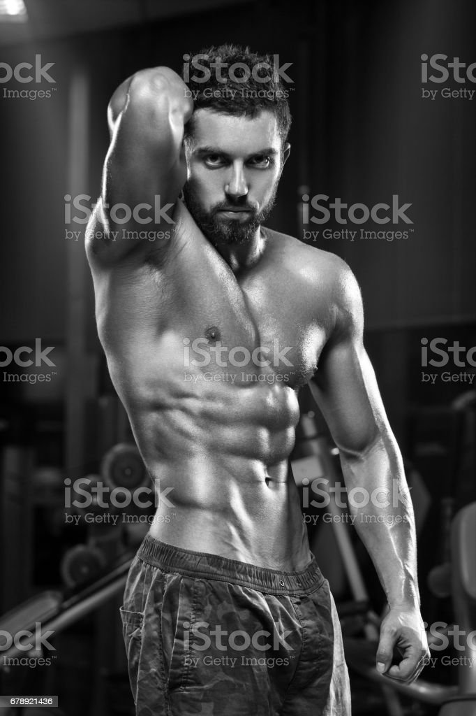Sexy muscular man in gym, shaped abdominal. Strong male naked torso abs, working out stock photo