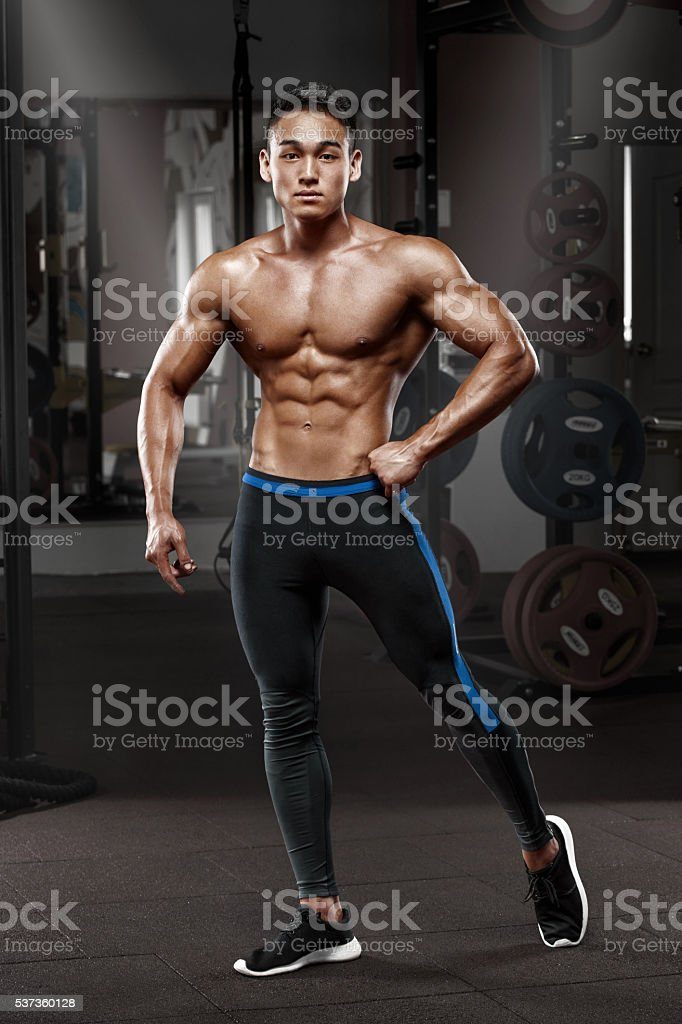 Sexy muscular man posing in gym, naked torso, working out stock photo