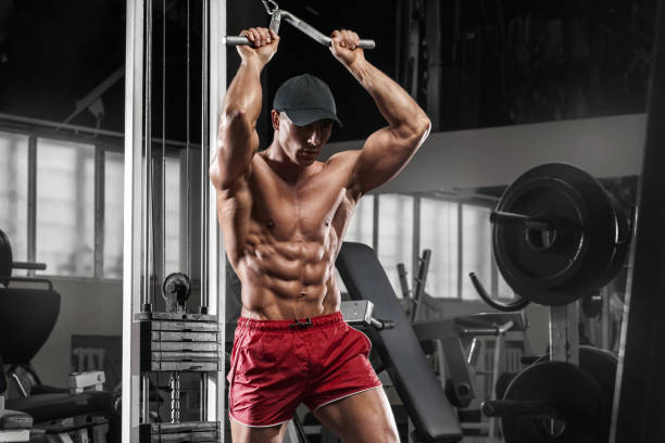 Sexy muscular man working out in gym doing exercises, strong male naked torso abs stock photo