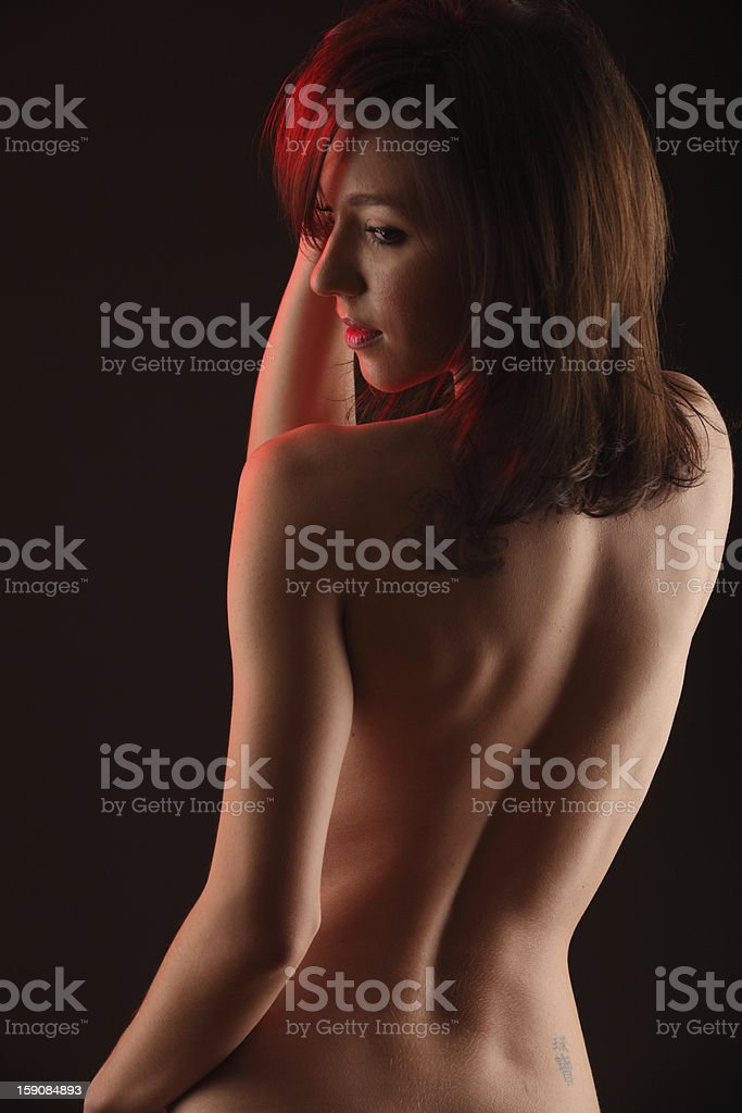 Sexy naked young woman looking over her left shoulder royalty-free stock photo