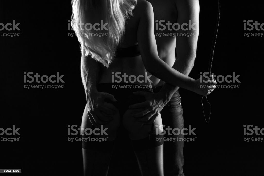 Sexy passionate couple with whip at night in darkness black and white Sexy passionate couple with whip at night in darkness, black and white Black And White Stock Photo