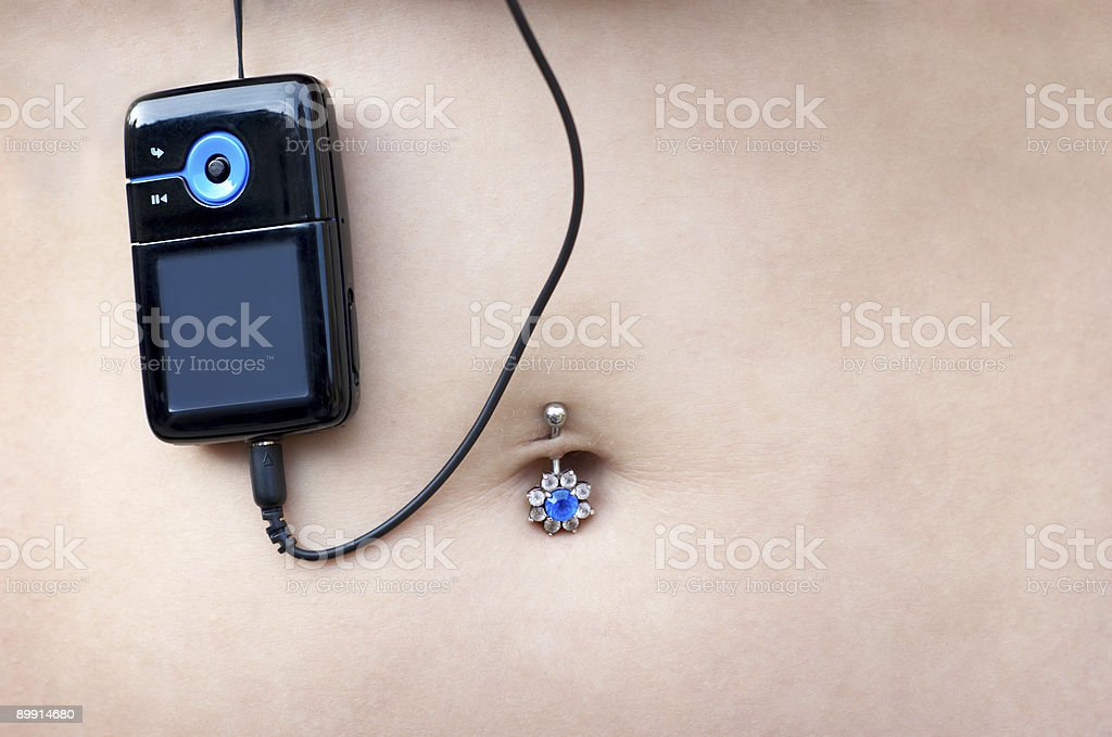 sexy pierced belly with mp3 player royalty-free stock photo