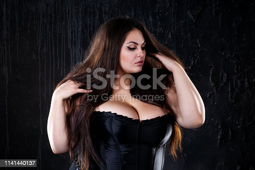 498310066istockphoto Sexy plus size model in black corset, fat woman with big natural breasts on dark background, body positive concept 1141440137