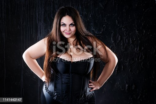 498310066istockphoto Sexy plus size model in black corset, fat woman with big natural breasts on dark background, body positive concept 1141440147