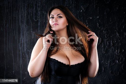 498310066istockphoto Sexy plus size model in black corset, fat woman with big natural breasts on dark background, body positive concept 1141440276