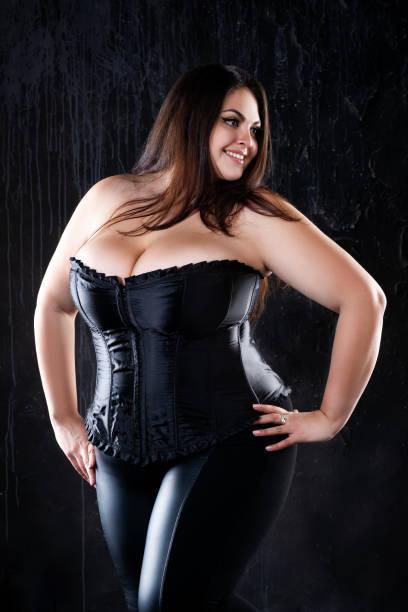 sexy plus größe modell in schwarzem korsett, fette frau mit großen natürlichen brüsten auf dunklem hintergrund, körper positives konzept - damen leggings übergrößen stock-fotos und bilder