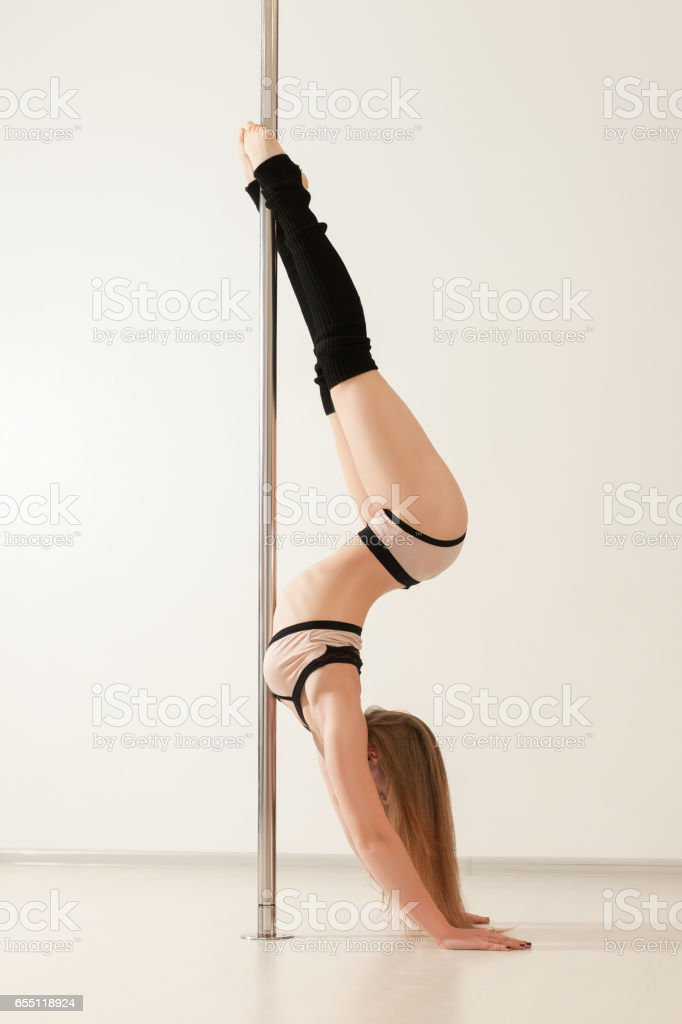 Sexy pole dance woman in lingerie upside down stock photo