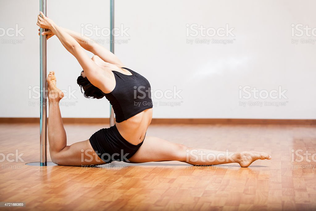 Sexy pole dancer stretching against pole stock photo