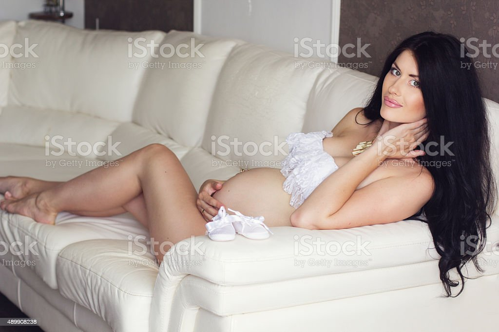 Sexy pregnant woman is wearing white lingerie at home stock photo