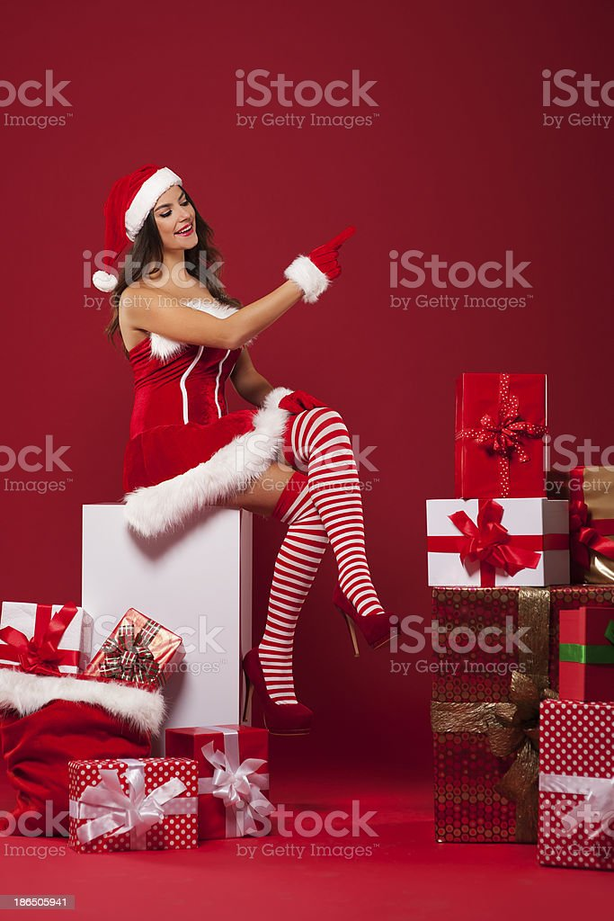 Sexy santa pointing at red copy space royalty-free stock photo