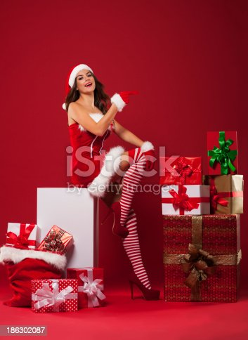 istock Sexy santa woman showing at copy space 186302087