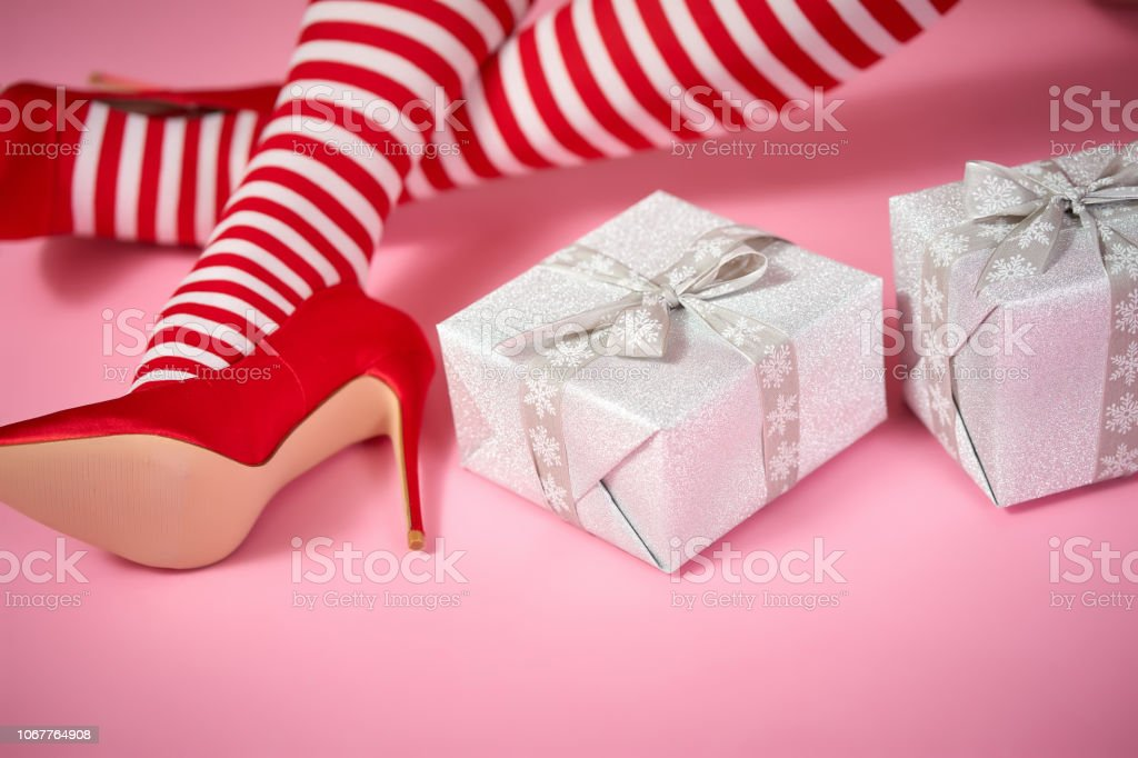 sexy santa woman's legs on a pink background and Christmas gifts – zdjęcie