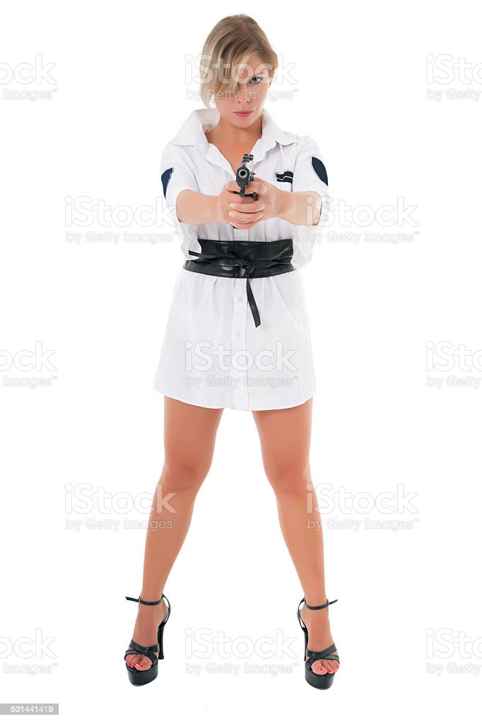 Sexy serious blonde in short tunic aiming with gun stock photo