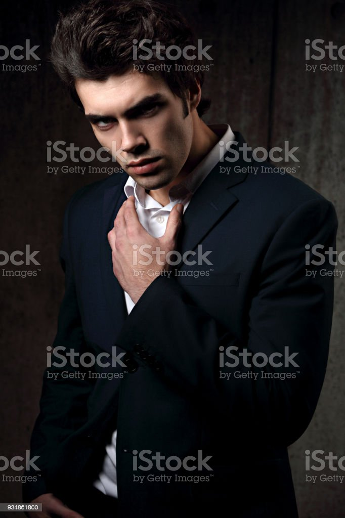 22e9b9ae Sexy serious handsome male model posing in blue fashion suit and white  style shirt on dark