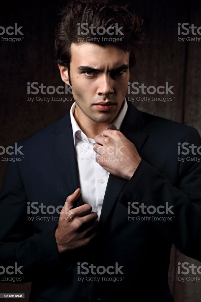 5b28aa5e Sexy serious handsome man posing in blue fashion suit and white style shirt  on dark shadow