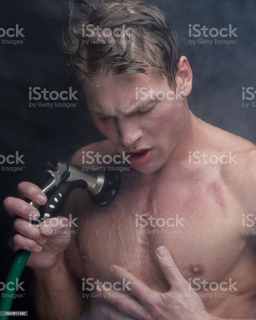 Sexy shirtless man getting wet with a hose and standing in fog stock photo