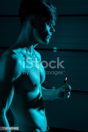sexy shirtless muscular man holding lighter in darkness
