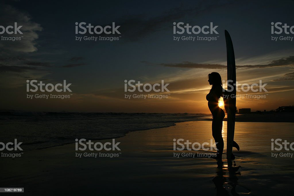 Sexy silhouette surfing sunset at beach stock photo