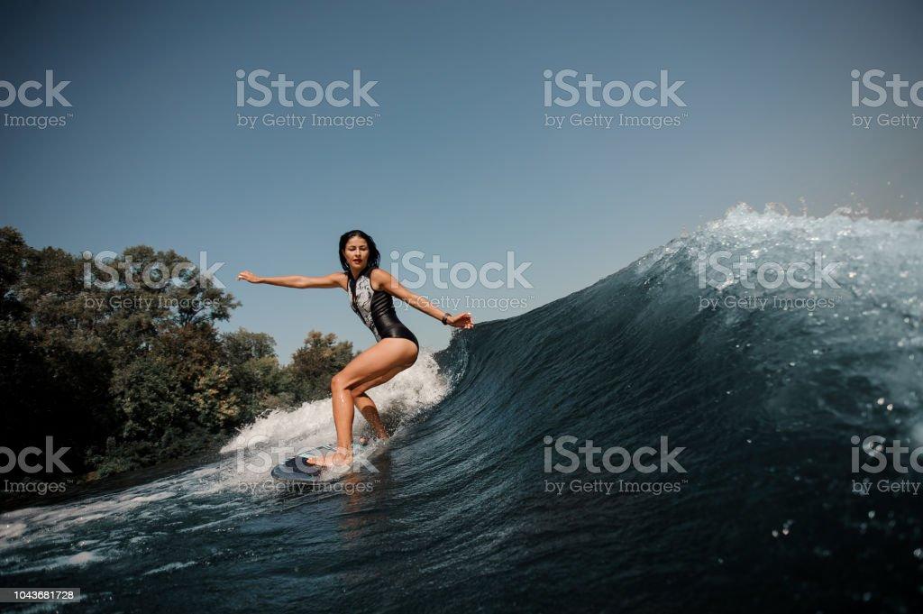 Sexy slim brunette woman wakesurfing on a board down the blue water...