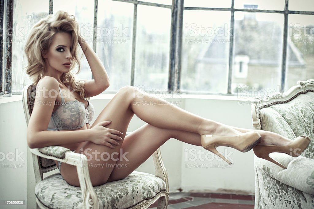 Sexy smiling woman relaxing in bed covering her breast. stock photo