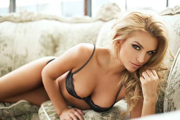 sexy donna sorridente rilassante sul letto con il suo seno. - donna seducente foto e immagini stock